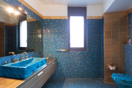 Bathroom with blue mosaic and large mirror. No one inside 写真素材