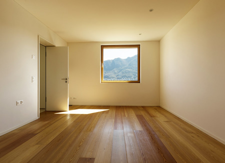 Interior of an empty room with a wooden floor and a nice window in the opposite wall 写真素材