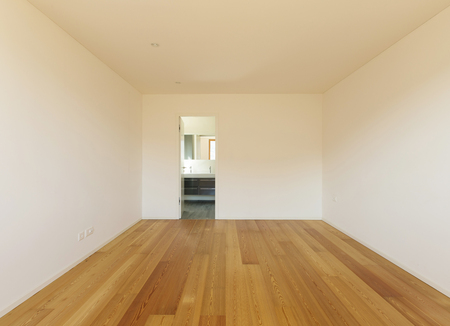 Empty bedroom with wooden floor and white walls.