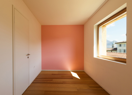 Empty bedroom with wooden floor and a rose-painted wall.