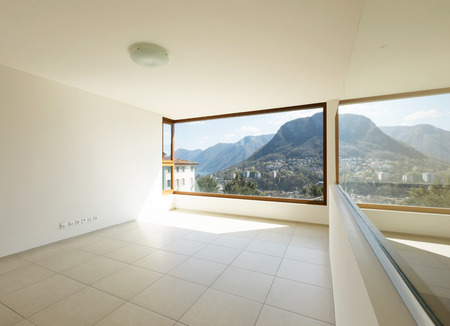 Interior of a wide room with a big window and view on the mountain. Nobody inside. Archivio Fotografico - 121645802