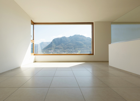 Interior of a wide room with a big window and view on the mountain. Nobody inside.