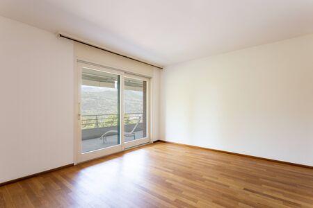 Slaapkamer met witte muren en parket. Raam met uitzicht op het meer. Niemand binnen