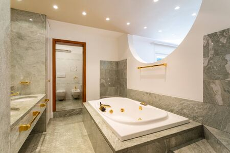 Luxury bathroom with large hydromassage, green marble and gold sinks. Nobody inside Фото со стока
