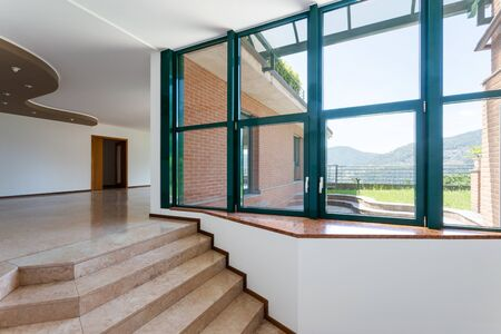 Entrance of luxury apartment with marble and large windows to the private garden. Nobody inside Foto de archivo - 129223515