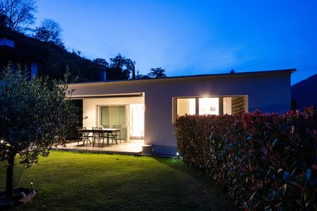 Exterior of a small modern house with garden. Night situation Stockfoto