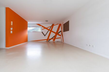 Front view of the room with white and orange walls. Resin floor. No one inside