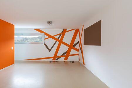 Vista frontal de la habitación con paredes blancas y naranjas. Suelo de resina. Nadie adentro