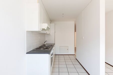 Empty room with vintage kitchen, white tiles and walls. Nobody inside Stock Photo
