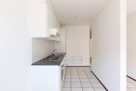 Pusty pokój z rocznika kuchnią, białymi płytkami i ścianami. Nikt w środku Zdjęcie Seryjne