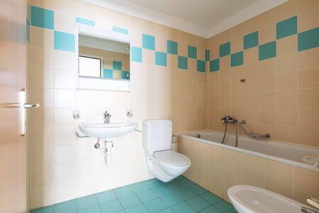 Baño vintage con azulejos beiges y azules. Nadie adentro.