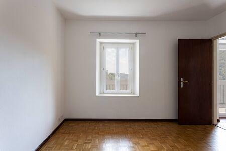 Pièce vide aux murs blancs et fenêtre donnant sur la nature. Personne à l'intérieur de la pièce.