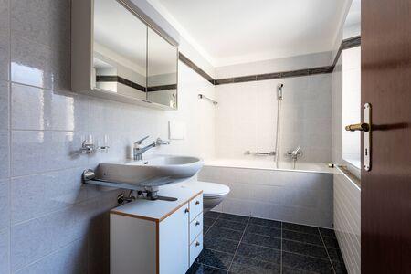 Bathroom with black tiles and large bathtub. Nobody inside
