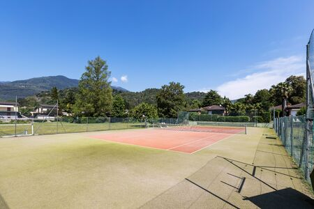 Private tennis court on a beautiful sunny summer day. Nobody inside Banco de Imagens