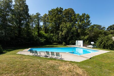 Private pool on a beautiful sunny summer day. Nobody inside Banco de Imagens