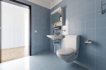 Bathroom with vintage blue tiles. Sink and toilet. Nobody inside.