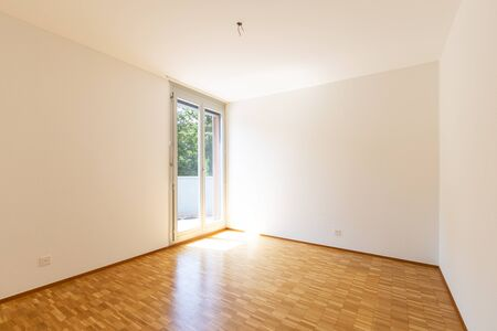 Empty room with white walls and window with balcony. 1970s parquet. Nobody inside