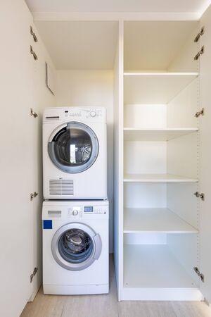 Vista frontal de la lavadora y secadora en un armario blanco con puertas abiertas. Nadie adentro Foto de archivo