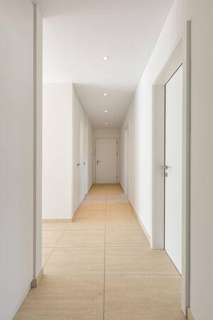 Corridoio con pavimento in travertino, pareti bianche e armadi a muro. Nessuno dentro