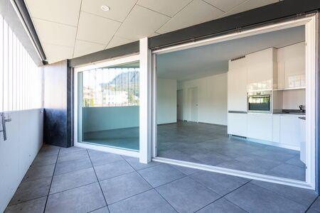 Cucina bianca moderna in appartamento vuoto con pareti bianche. Piastrelle scure. Nessuno dentro