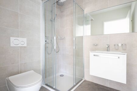 Modern minimal bathroom with large tiles and shower. Nobody inside