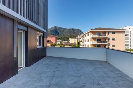 Gran terraza con grandes baldosas de mármol con vistas a las colinas suizas del Tesino. Nadie adentro. Día soleado, cielo azul