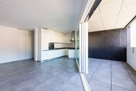 Moderne weiße Küche in leerer Wohnung mit weißen Wänden. Dunkle Fliesen. Niemand drin