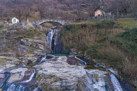 Romantic landscape of southern Switzerland, a waterfall of water a stone bridge and a green puddle. Very romantic Banco de Imagens