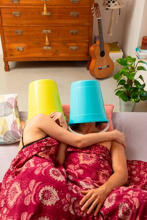 Young couple in bed with a bucket on their heads, they make love or rest, however they don't talk to each other. Standard-Bild