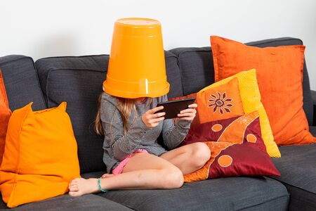 Little girl sitting on a sofa at home with a bucket on her head plays with the tablet