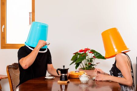 Young loving couple drinks coffee in the dining room with a bucket on their heads. Unreal situation and concept of non-communication Standard-Bild