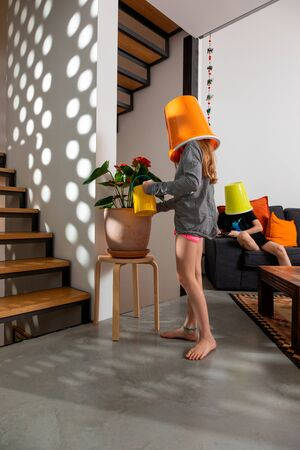 Little girl with bucket on her head takes care of the flowers of her home, the staircase is in wood. Standard-Bild