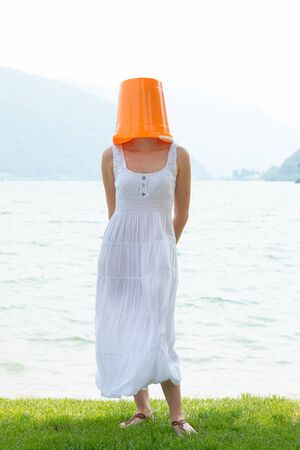 young woman standing by the lake with an orange bucket on her head and a long dress and white skirt