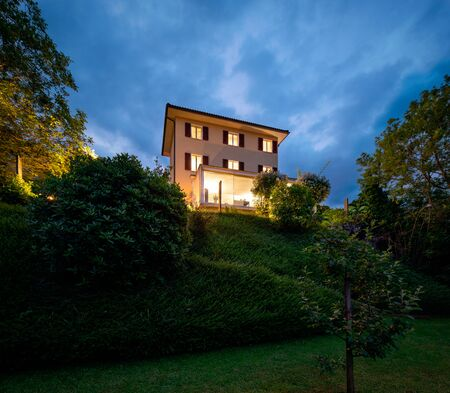Beautiful house in the middle of the greenery with a modern reinforced concrete connection and a large window. The photo was taken in the evening and with a feeling of natural romance. The dream of a fairy tale. Standard-Bild