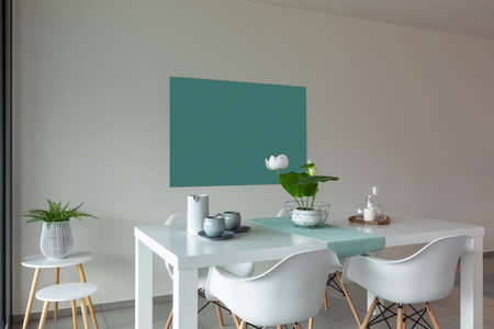 Dining room with white table and white chairs. Modern and linear furniture.