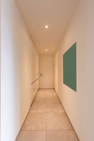 Interior of a long corridor of an apartment. At the bottom a closed door Standard-Bild
