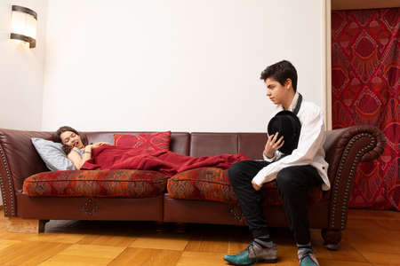 Girl lying on the sofa with a blanket and a young boy is sitting desperately dressed elegantly Stockfoto