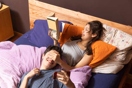 Young couple in bed. She reads a book while playing with him trying to look at the phone