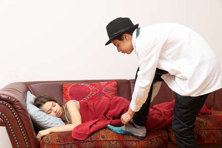 Young elegant dressed businessman tries to tie his shoes while the girl is lying on the sofa covered by a blanket
