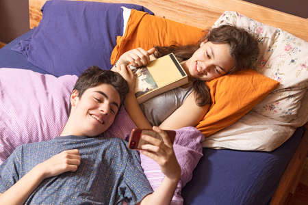 Young couple is lying in bed. They both look at the phone while they have fun Banco de Imagens - 151813894