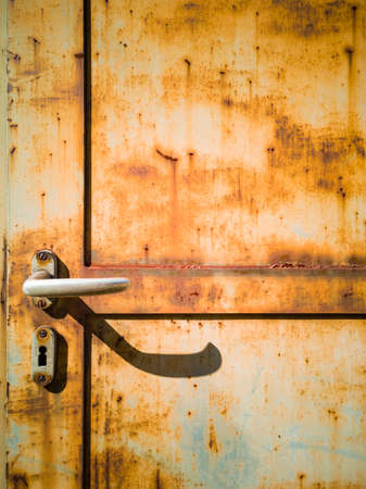 Detail of a rusty door of a factory. Frontal view. Nobody inside. Copy space