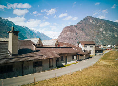 Abandoned factory front view in the valley. Glimpse of Biasca in Switzerland. Nobody inside Standard-Bild