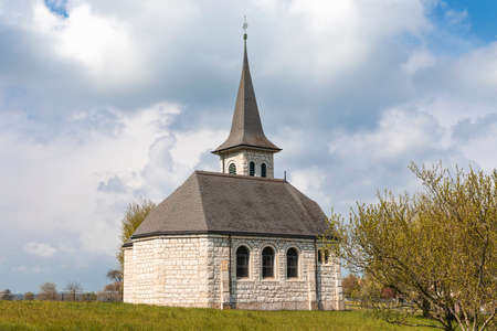 Characteristic church in the green field in the Swiss Alps of the Canton Jura. Nobody inside. Cloudy day. Standard-Bild