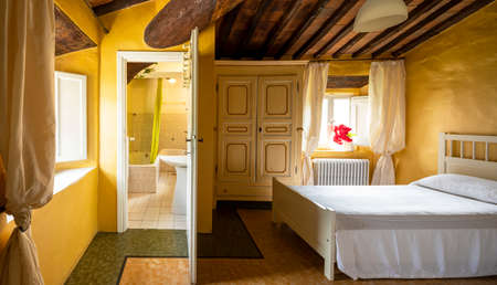 Old double bedroom with bathroom inside. The walls are yellow