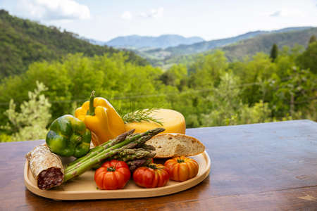 Plank of wood full of food from the land of Tuscany in Italy, peppers, salami, tomatoes. View on the Italian nature full of green plants. Standard-Bild
