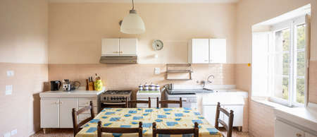 Interior of an old kitchen, almost antique, a table in the middle, the space is large and it is also bright. There is no style, they are pieces of furniture put together without aesthetic taste and the whole form romanticism