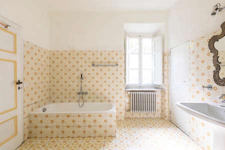 Interior of an old bathroom with window and bathtub.