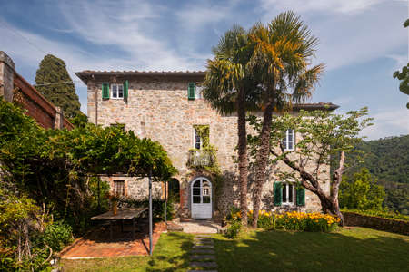 Beautiful Italian farmhouse in Tuscany surrounded by nature with a large garden. The season is summer and the sun is shining. Standard-Bild