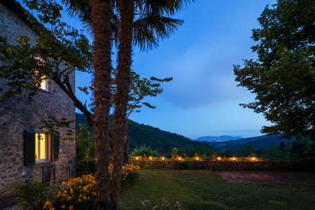 House or cottage at sunset with a beautiful garden in Tuscany. The place is romantic and makes you dream. It is almost evening the silence can be heard from the photograph