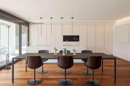 Interior of a modern apartment, with dining room and open kitchen. Front view hardwood floors. Nobody inside, the table seats six.